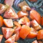 Closeup of tomatoes put into the pan - Lentil Potato Medley