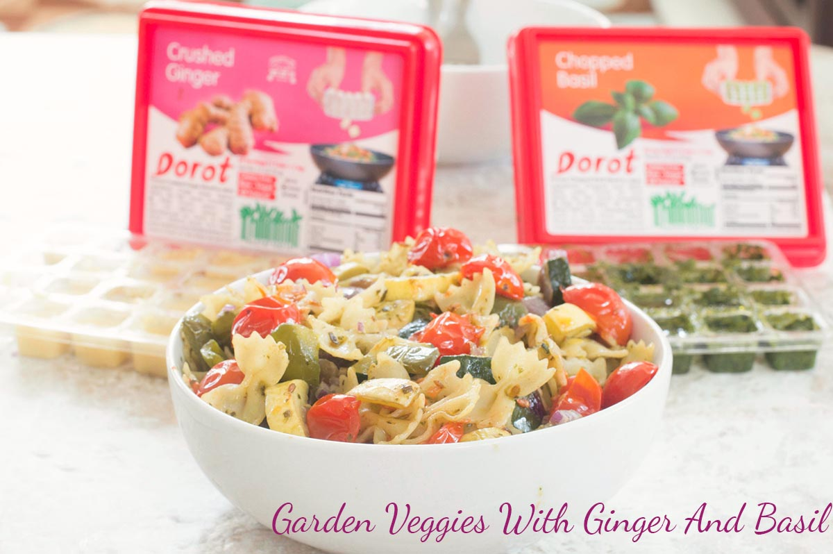Front view of Farfalle pasta in a white bowl filled with roasted veggies. Open Dorot Containers in the background