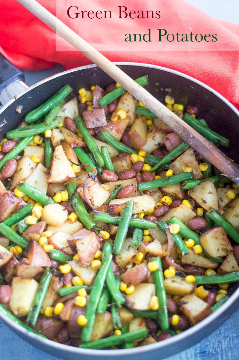 Overhead view of a pan filled with cooked green beans, potatoes, corn and red kidney beans