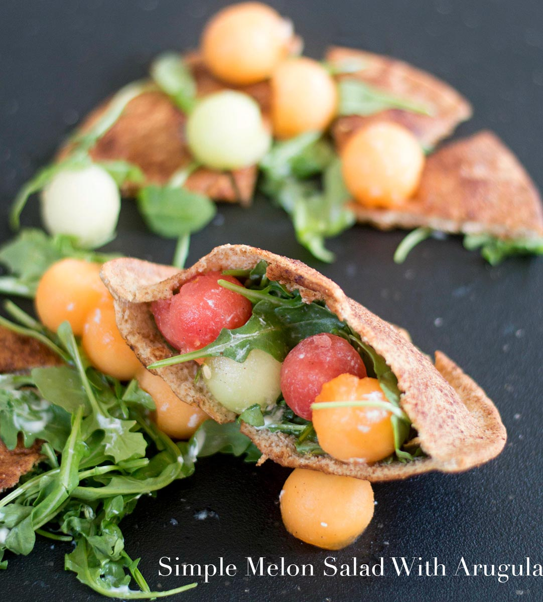 Melon Balls in a pita pocket and surrounded by more melon balls, arugula and pita chips
