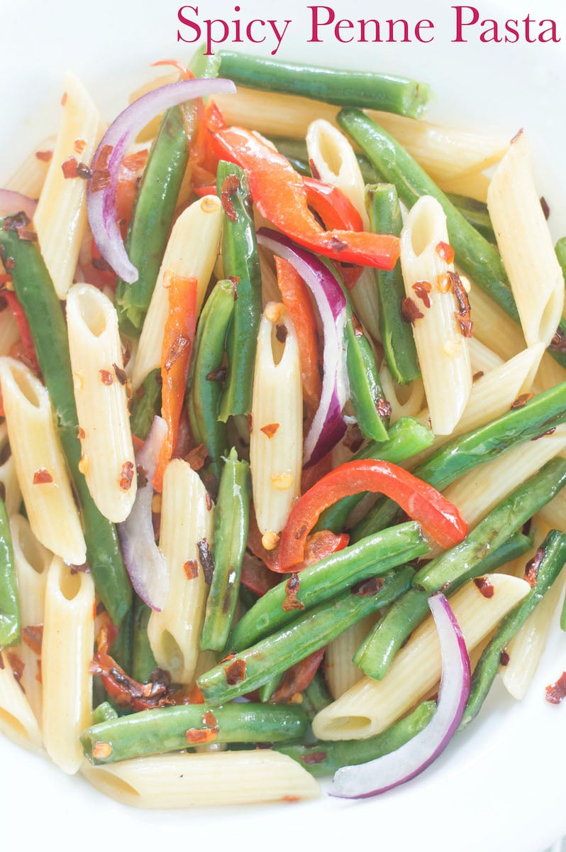 Closeup view of a plate with Penne Pasta, Green Beans, Bell Pepper and Onions