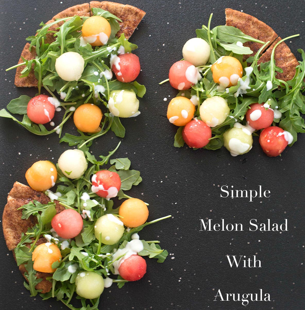 Overhead view of melon balls on arugula and pita bread in 3 of the 4 corners