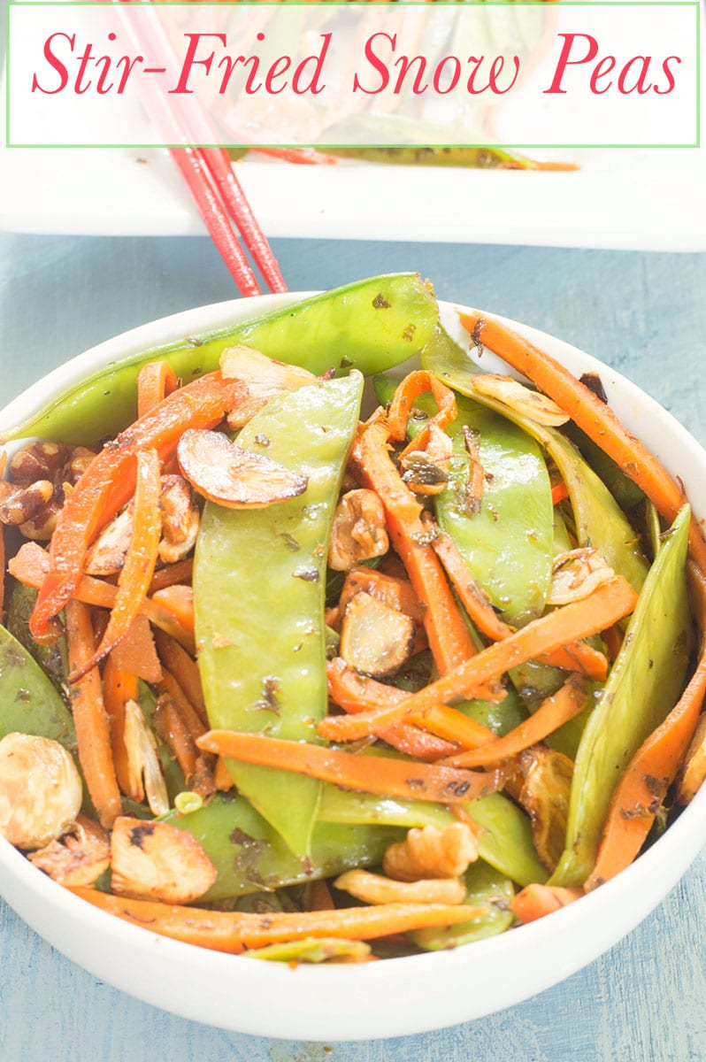 A White bowl with snow peas, carrots and ginger stir fried