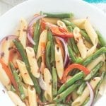 Vegan Spicy Penne Pasta with roasted green beans and red bell peppers. Topped with simple lemon vinaigrette and red pepper flakes. Under 30 minutes to make
