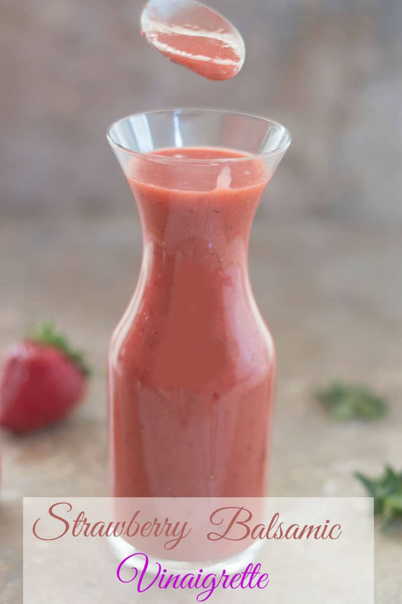 A Filled Spoon over Strawberry Balsamic Vinaigrette in a glass jar with strawberries in the background