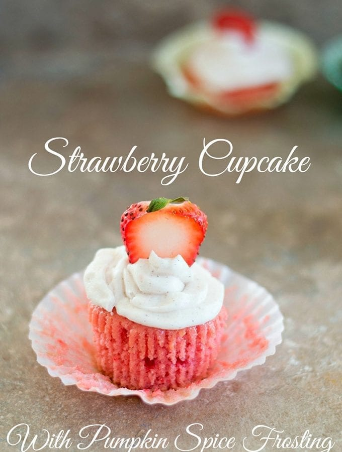 Front View of a Strawberry Cupcake With Frosting and a Sliced Strawberry. In the Background, there is One More Cupcakes