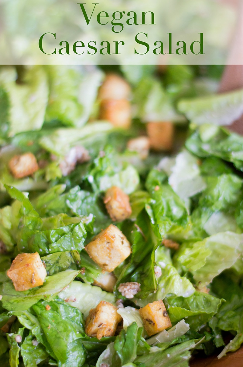 Closeup view of Roughly Chopped Romaine Lettuce, Stir-fried Tofu Cubes and Shredded Coconut. Top of the Photo Has Vegan Caesar Salad in Didot Font