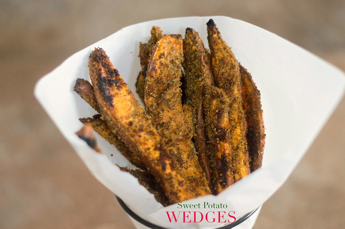 Front View of Sweet Potato Wedges Lined Upright In a Cone Made From Parchment Paper and Placed in a Cone-Shaped Black Fry Holder