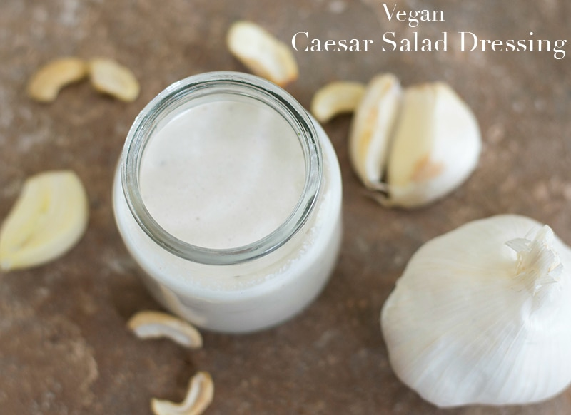 Overhead View of a Small Glass Jar filled with Vegan Caesar Salad Dressing. Jar is Surrounded by Cloves of Garlic and Cashews. One Head of Garlic is Visible on the Bottom Right of the Screen