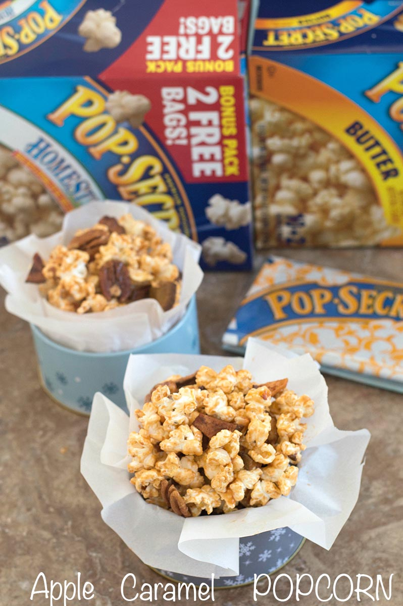 Front view of apple caramel popcorn in holiday containers surrounded by Pop Secret boxes