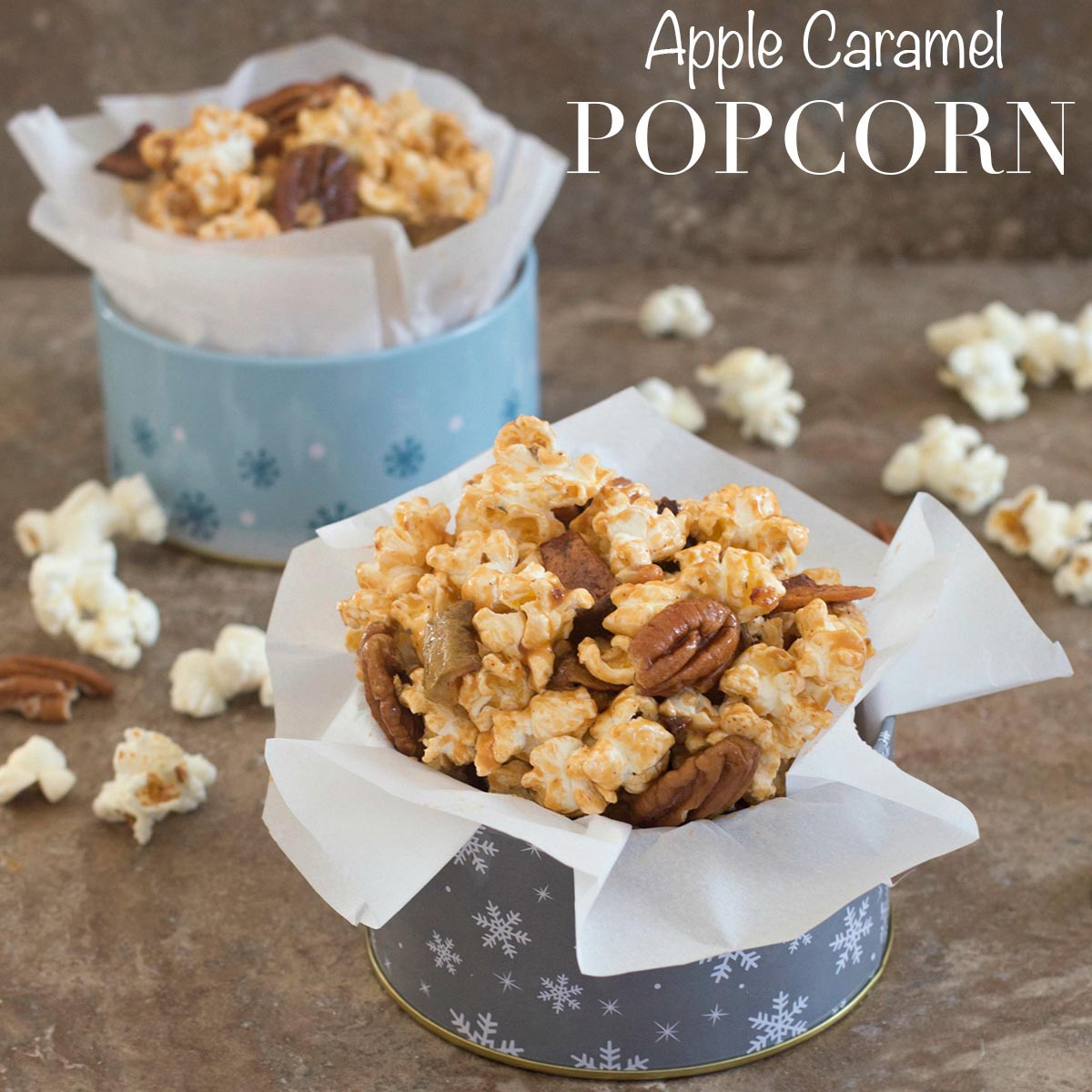 Front view of apple caramel popcorn in holiday containers