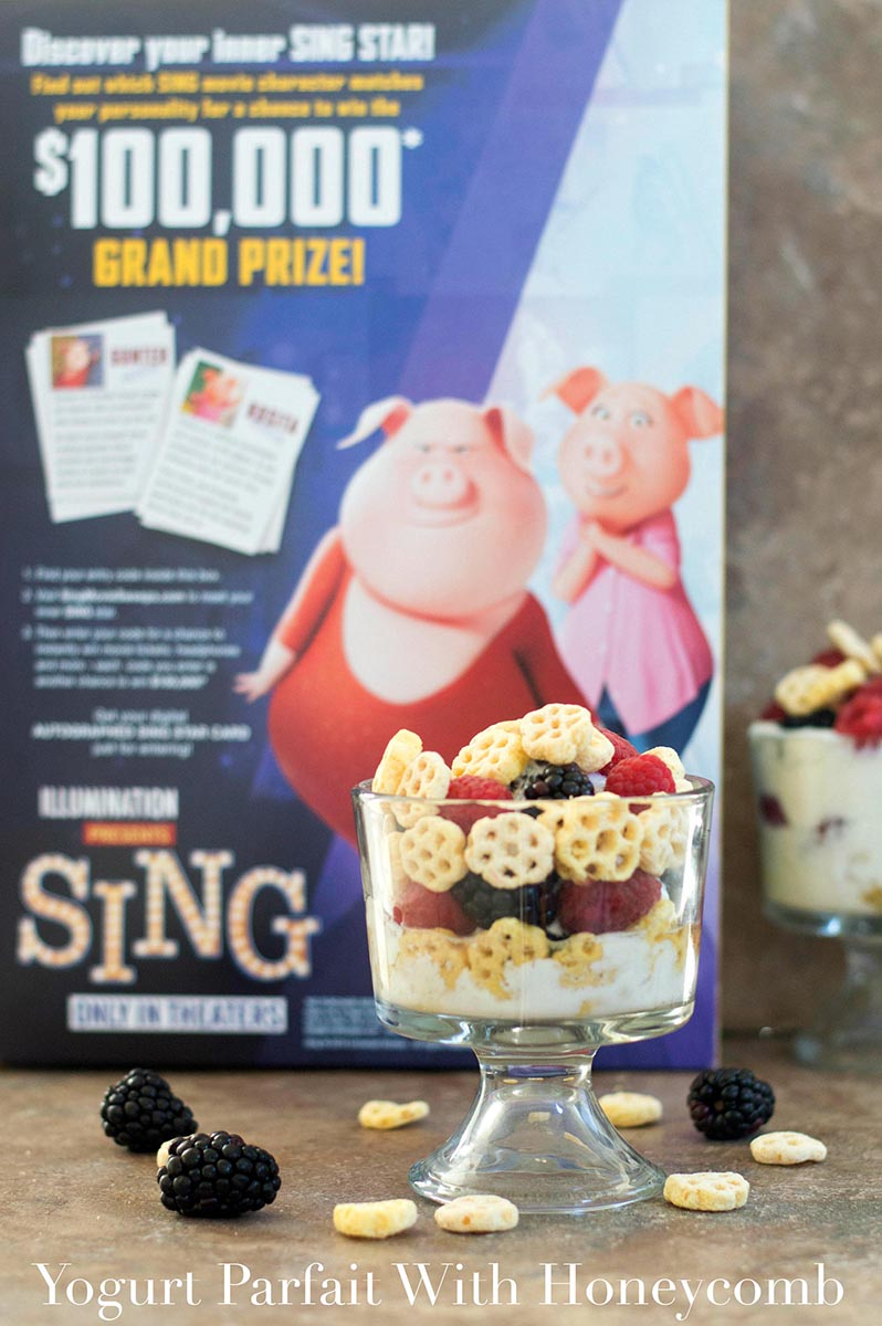 Front view of a glass bowl with yogurt, honecomb serial, raspberry and blackberry. Honeycomb Cereal box in the background - Yogurt Parfait