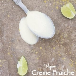 A Spoon Filled with Creme Fraiche is Laying Flat on a Brown Surface with the Liquid Spilled Around the Spoon. There are Slices of Lime and Nutritional Yeast Strewn Around