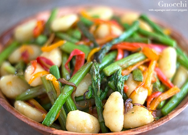 Closeup view of brown bowl with gnocchi, asparagus and red bell peppers