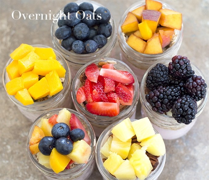 Overhead View of 6 Mason Jars Arranged in a Circle and 1 jar in the Middle. Each Jar is Topped With Fruits