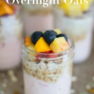 Front View of One Mason Jar Filled With Layers of Yogurt, Oats and Fruits. In the Background, 3 other Filled Mason Jars are Blurred