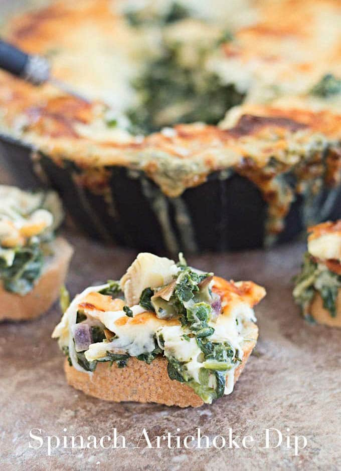 A Piece of Bread Topped with Melted Cheese, Spinach and Artichoke.