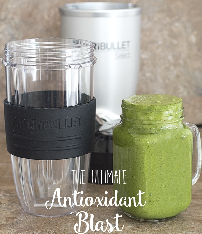Front view of the nutribullet container next to a glass filled with the ultimate antioxidant blast. The Nutribullet Select base is in the background