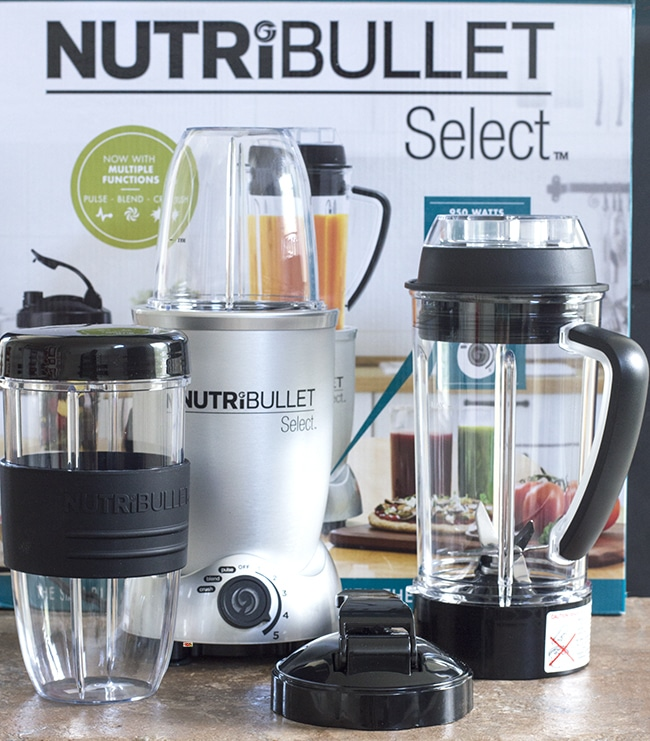Front View of the contents of the NutriBullet Select Box which includes the blender base, containers, blade and lids. The box itself is visible in the background - the ultimate antioxidant blast
