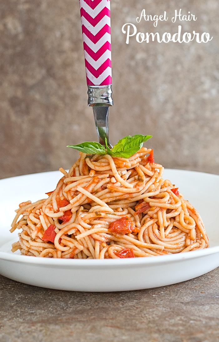Thin Spaghetti in a White Bowl Arranged in a Cone Shape and A Fork With Chevron Pattern Handle Stuck on the Top of the Cone Shape. 2 Leaved Basil Next to the Fork For Garnish