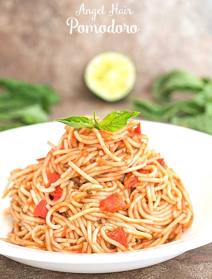 Closeup view of Cooked Thin Spaghetti with Tomatoes on a White Plate. Topped With 2 Leaves of Basil for Garnish. A Partially Squeezed Half Lime and Basil Leaves strewn in the background