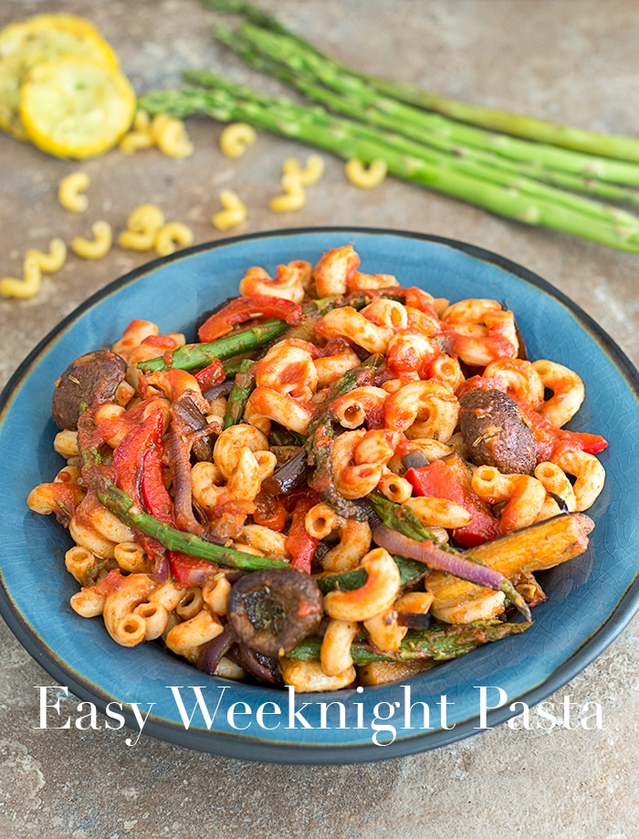 55° Angle View of a Blue Plate with Cooked Elbow Pasta, Roasted Veggies and Mixed with Marinara Sauce. In the Background, Uncooked Asparagus sticks are visible in the right, Uncooked Elbow Pasta Next to it and 3 Pieces of Cooked Circular Shaped Yellow Squash - Easy Weeknight Pasta