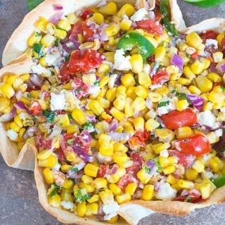 Overhead Photo of Mexican Street Corn in a Taco Bowl with Half of a Partilally Juiced Lime, Cilantro Leaves and Cherry Tomatoes at the Top and 2 Slices of Jalapeno at the Bottom of the Photo