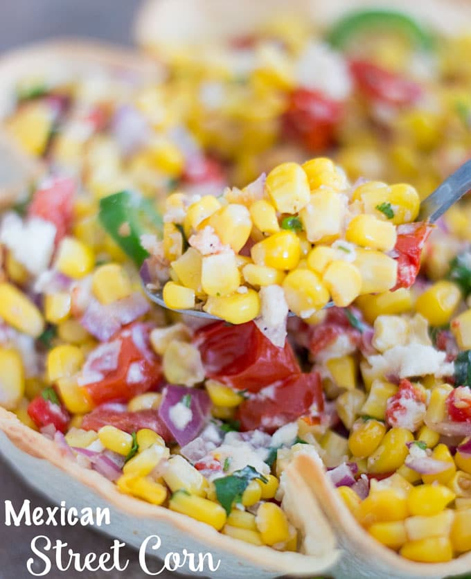 Closeup of Mexican Street Corn on a spoon with bowl below