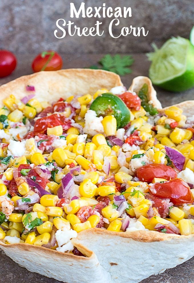 Front View of Mexican Street Corn in a Taco Bowl with Partially Juiced Lime, Cilantro and Cherry Tomatoes in the background