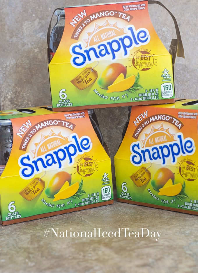 "2 cases of 6 Pack ""Takes 2 to Mango"" Snapple Tea Placed on a Brown Tile. 1/2 of a 6 Pack of Mango Tea Case Placed on Top of the Two Cases - Celebrating National Iced Tea Day"
