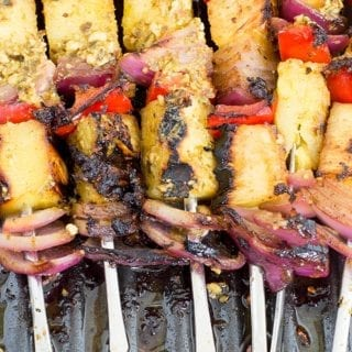 75° View of 6 Metal Skewers Filled with Fruits and Veggies. Each Skewer has a Grilled Pineapple Piece, a Red Bell Pepper and a Red Onion. Each Skewer has This Arrangement 3 Times