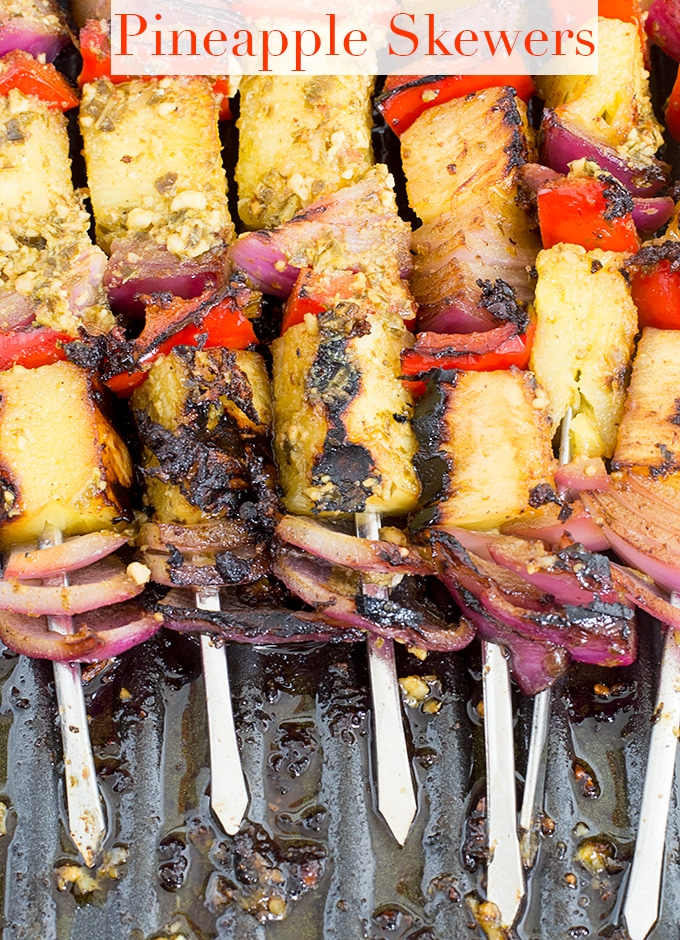 75° View of 6 Metal Skewers Filled with Fruits and Veggies. Each Skewer has a Grilled Pineapple Piece, a Red Bell Pepper and a Red Onion. Each Skewer has This Arrangement 3 Times - Pineapple Skewers