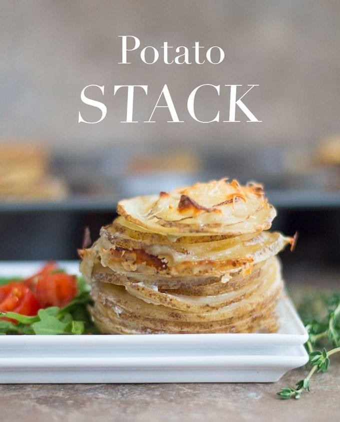On a White Plate, There Are Thin Slices of Cooked Idaho Potatoes Stacked on Top of Each Other and Topped with Melted Parmesan Cheese. On the Side of the Potatoes, There is a Simple Cherry Tomato and Arugula Salad. In the Background, a Muffin Tray Filled with Stacks of Cooked Potatoes is Blurred. Sprigs of Thyme are Placed to the Right of the White Dish