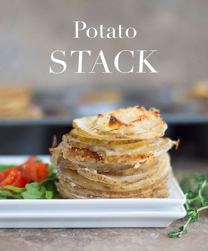 On a White Plate, There Are Thin Slices of Cooked Idaho Potatoes Stacked on Top of Each Other and Topped with Melted Parmesan Cheese. On the Side of the Potatoes, There is a Simple Cherry Tomato and Arugula Salad. In the Background, a Muffin Tray Filled with Stacks of Cooked Potatoes is Blurred. Sprigs of Thyme are Placed to the Right of the White Dish. Potato Stack