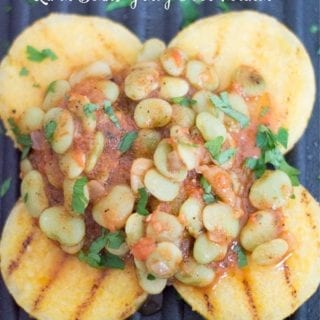 Overhead Photo of Lima Beans in a Light Tomato Gravy Topped on Four Small Rounds of Polenta Over a Black Calphalon Square Grill. Grill Marks Visible on the Polenta