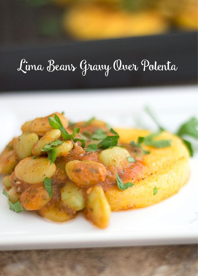 Front View of a Small Polenta Round Sitting on a Small White Plate. A Light Lima Beans in Tomato Gravy Topped on the Left of the Polenta. Garnished with Italian Parsley. The Side of a Black Calphalon Stove Top Square Grill is Visible in the Background. The Grill has Polenta Rounds With Lima Beans Curry