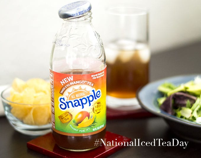 Takes 2 to Mango Snapple Bottle is Filled Half Way. Right Behind it and to the Left, a Small Bowl with Chips is Partially Visible. To the Right of the Bottle, a Blue Plate with Salad Greens is Partly Visible. There is a Glass Filled Half Way with Iced Tea and Ice Cubes is Visible - Celebrating National Iced Tea Day