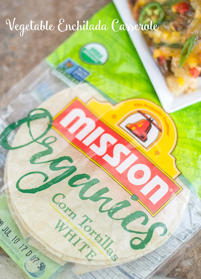 A Packet of Mission Organics White Corn Tortillas is Placed Flat on a Tile. On the Top Right of the Image, Part of a Cheesy Vegetarian Enchilada Casserole on a Square White Plate is Visible