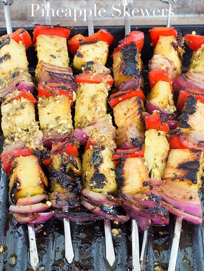 Overhead View of 6 Metal Skewers Filled with Fruits and Veggies. Each Skewer has a Grilled Pineapple Piece, a Red Bell Pepper and a Red Onion. Each Skewer has This Arrangement 3 Times