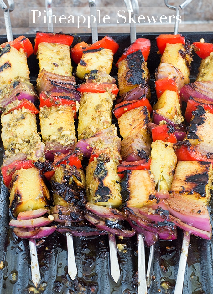 Overhead View of 6 Metal Skewers Filled with Fruits and Veggies. Each Skewer has a Grilled Pineapple Piece, a Red Bell Pepper and a Red Onion. Each Skewer has This Arrangement 3 Times - Pineapple Skewers