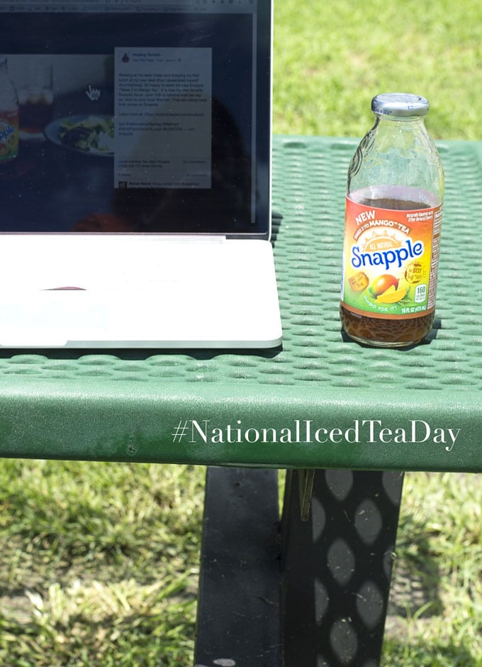 A MacBook Laptop Sitting on a Green Park Bench with a Mesh Top. Snapple Bottle Partially Consumed is to the Right of the Laptop. Their is Grass Surrounding the Bench - Celebrating National Iced Tea Day