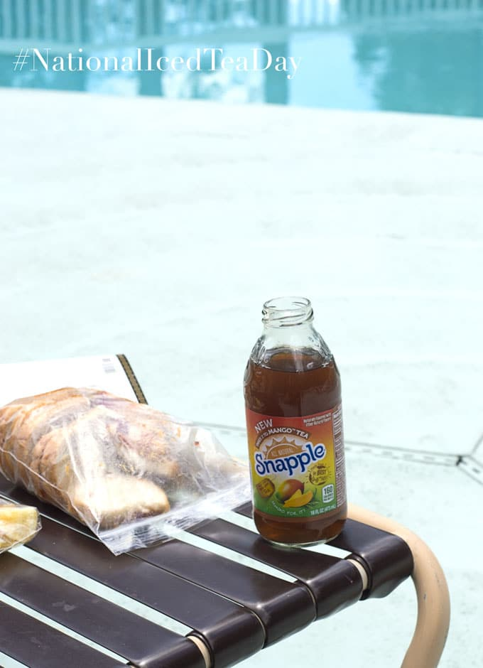 An Open Bottle of Snapple Takes 2 to Mango Placed at the Edge of a Pool Chair. A Ziploc Bag with PB&J Sandwiches is Next to the Snapple. Behind the Sandwiches a Book is Partially Visible. In the Distance, the Swimming Pool is Partially Visible - Celebrating National Iced Tea Day