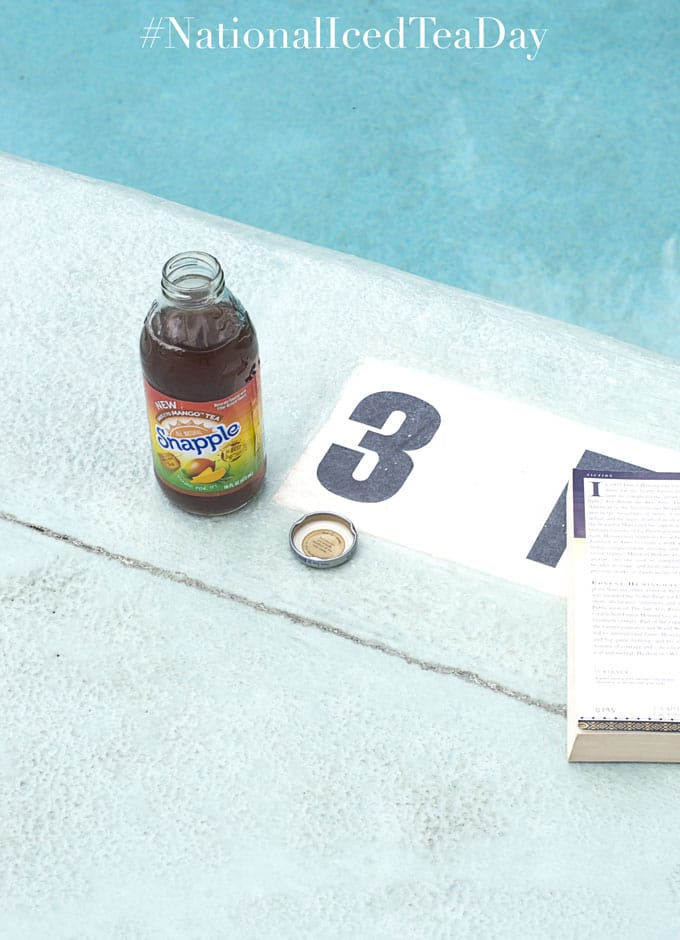 "An Open Bottle of Snapple Mango Tea with its Lid Next to it. The Number 3 is Visible and a Book is Partially Covering the Letters ""FT"". The Blue Waters of a Swimming Pool is Partly Visible - Celebrating National Iced Tea Day"