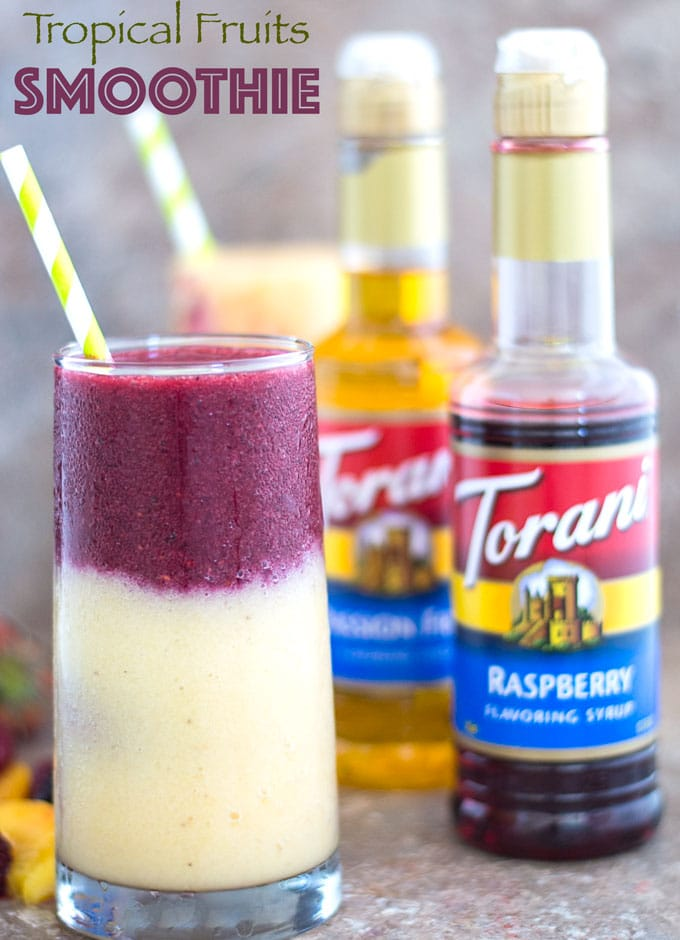 Front View of a Glass on the Left with a Layer of Yellow Smoothie Filled 3/4 of the Way. The Second Layer is a Purple Colored Smoothie and Topped with a Green and White Stripped Straw. To the Left of the Glass and at the Bottom, a Few Fruits are Partially Visible. Behind the Glass and to the Right, an Opened Torani Raspberry Flavoring Syrup is Visible. There is an Opened Torani Passion Fruit Flavoring Syrup Right Behind it Which is Partially Blurred. In the Distant Background, Another Smoothie Glass With a Green-white Stripped Straw is Partially Visible.