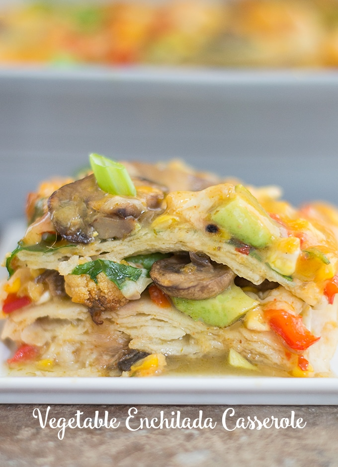 Front View of a Stack of the Vegetable Enchilada Casserole Is Visible. The Stack is Made up of Layers of Corn Tortillas and Roasted Vegetables. Topped with Mushrooms, melted Cheese, Avocado, and Spring Onions. In the Background, a Grey Casserole Dish is Partially Visible and Blurred.