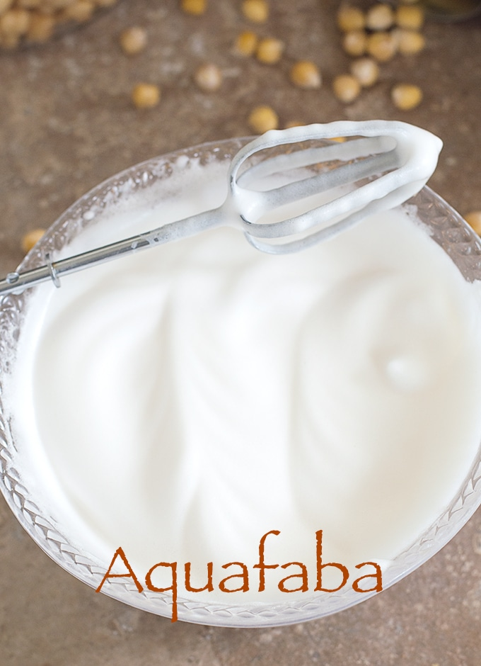 Overhead View of a Hand Mixer Beater Resting Diagonally on a Clear White Bowl Filled With Aquafaba. How To Make Aquafaba