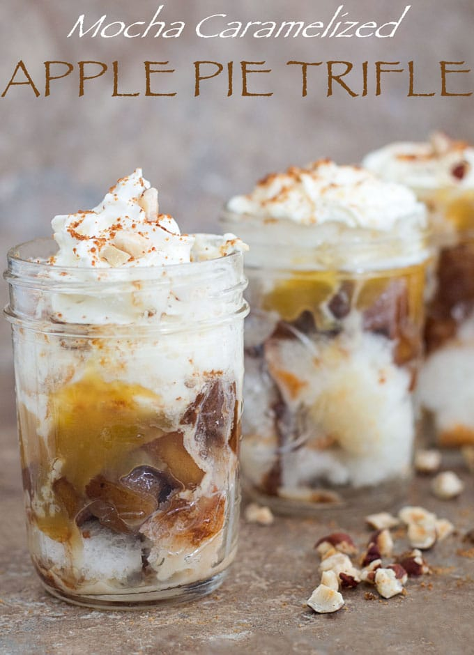 Front view of 3 apple pie trifle in mason jars arranged diagonally. Cinnamon stickes, hazelnut and cubed Angel Food cake surround the jars