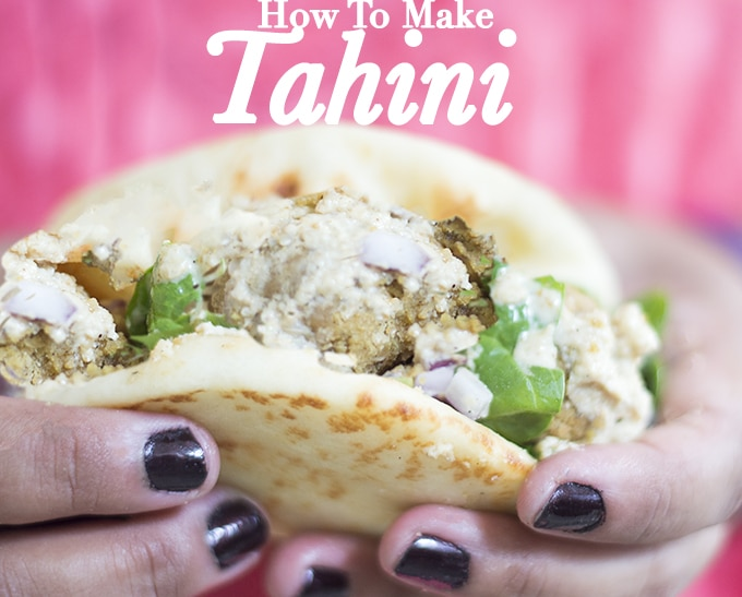 Front View of a Falafel Pita Sandwich Held by the Author Wearing an Orange Top. How to Make Tahini?