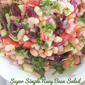 Closeup and Overhead View of White Bowl Containing Navy Beans, Chopped Campari Tomatoes, Cucumber, Dried Cranberries, Red Onions and Garnished With Chopped Curley Parsley. Super Simple Navy Bean Salad in Green Font is at the Bottom of the Photo