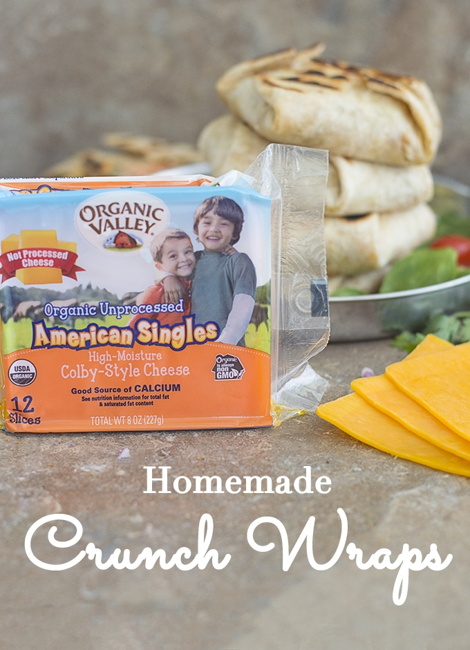 In the Forefornt, An Unopened Pack of Organic Valley American Singles is Upright. Next to it, 3 American Singles are Fanned out. In the Background, A Stack of Four Mini Crunch Wraps on a Stainless Steel Round Plate. Spinach, Veggie Chips, Cherry Tomatoes and Cilantro Strewn About